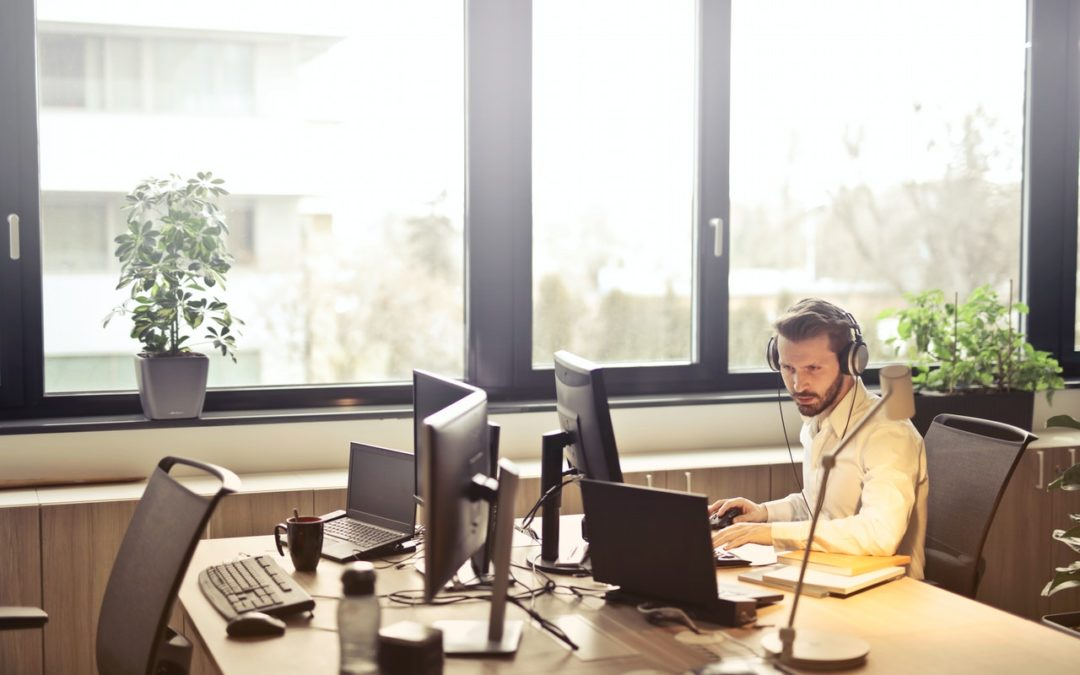 Man With Headphones On Computer At Office